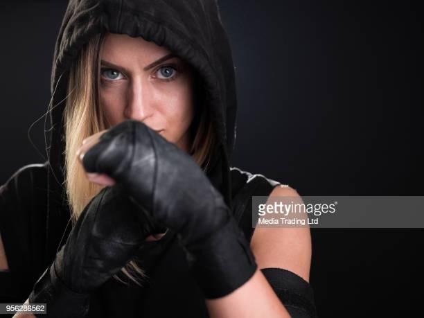 Chasseur femme avec capuche posant en position regardant la caméra de combat