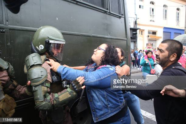 A woman fights against a police officer during a demonstration as part of the International Women's Day on March 8 2019 in Santiago Chile