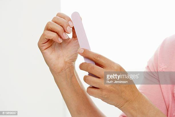 Woman filing nails, close up