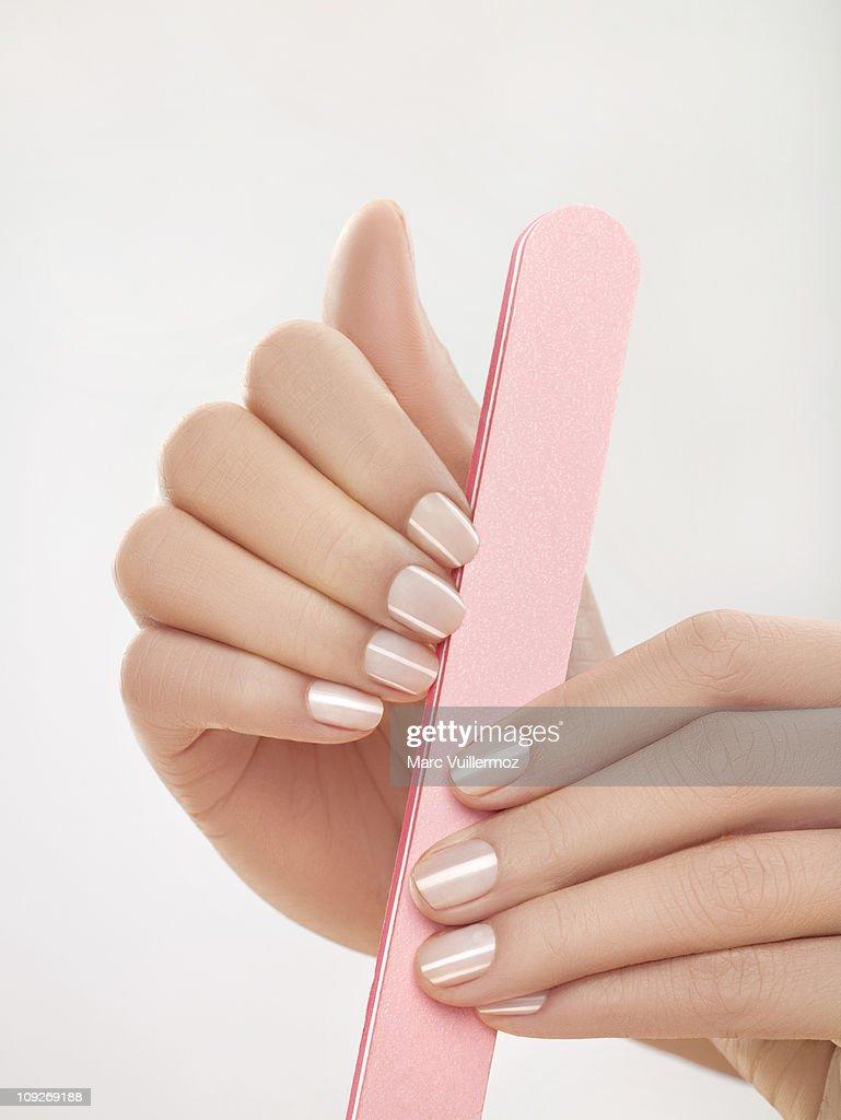 Woman filing nails, close-up : Stock Photo