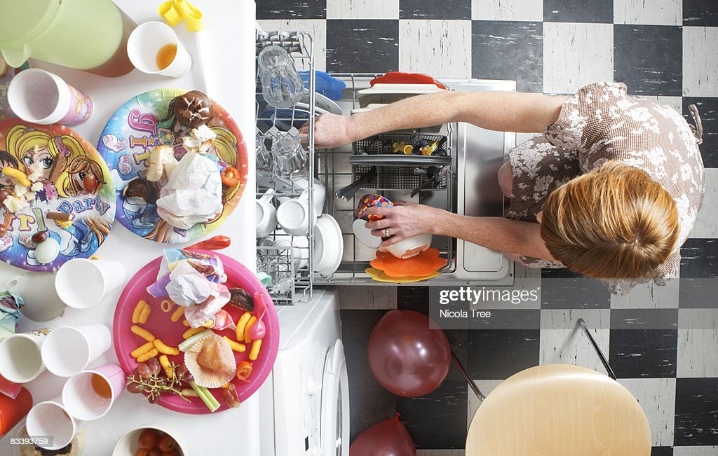 A woman filling a dishwasher after a party. : Stock Photo