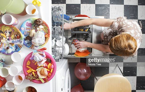 a woman filling a dishwasher after a party. - cleaning after party stock pictures, royalty-free photos & images