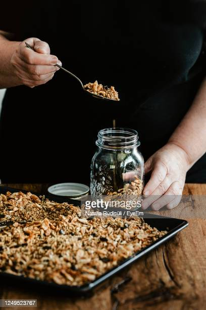 woman filling a mason jar with homemade granola. healthy vegan snack easily prepared at home. - granola stock pictures, royalty-free photos & images
