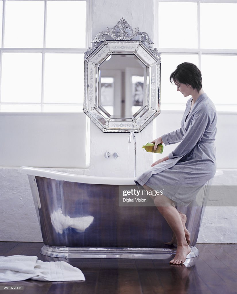 Woman Filling a Modern Metallic Bath : Stock Photo