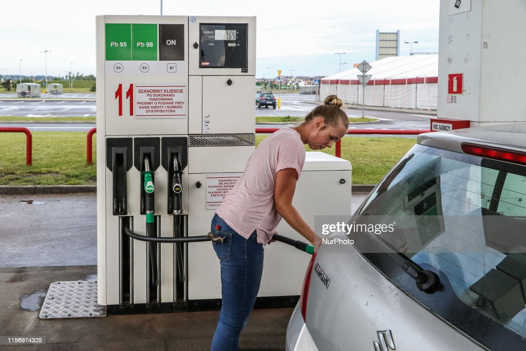 Woman Filling A Silver Suzuki Swift Car With Petrol At A