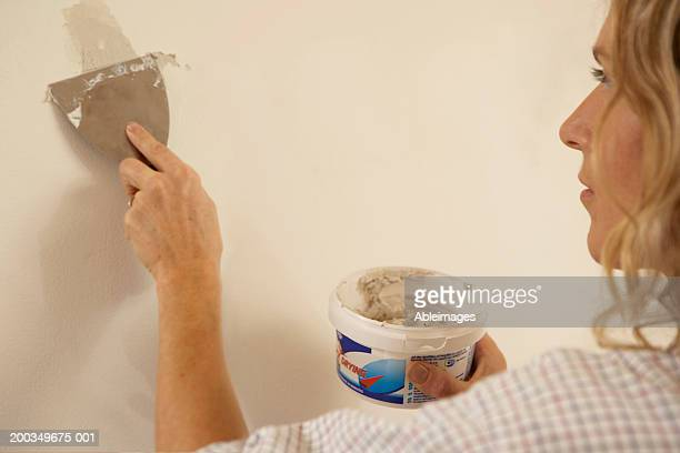 Woman filling hole in wall with multi-purpose filler, close-up