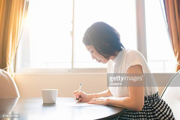 woman filling out paperwork - form filling stock photos and pictures