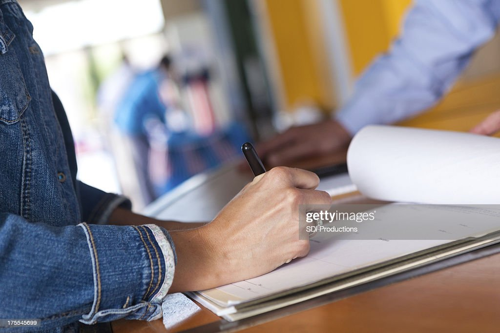 Woman filling out registration form at an event : Stock Photo