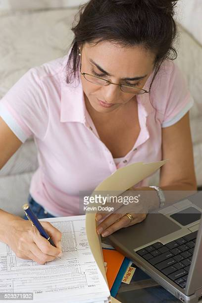 Woman Filling Out Tax Form at Home