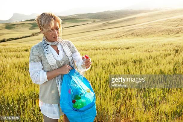 mujer llenado papelera de reciclaje - mujeres de mediana edad fotografías e imágenes de stock