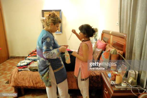 a woman filling suitcase with travel clothes and things with the help of her daughter - punjab university stock pictures, royalty-free photos & images
