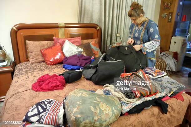 a woman filling travel bag with travel clothes and other things - punjab university stock pictures, royalty-free photos & images