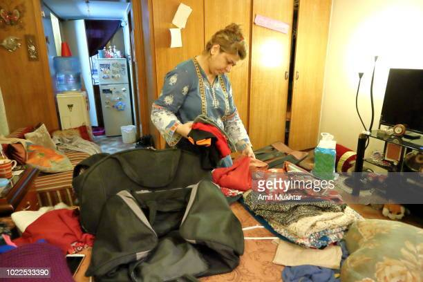 a woman filling travel bag with travel clothes and things - punjab university stock pictures, royalty-free photos & images