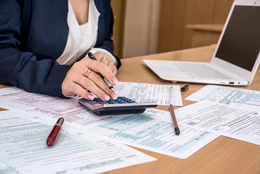 Woman filling US tax form 979040336