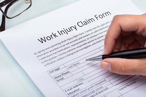 Woman Filling Work Injury Claim Form 1042650458