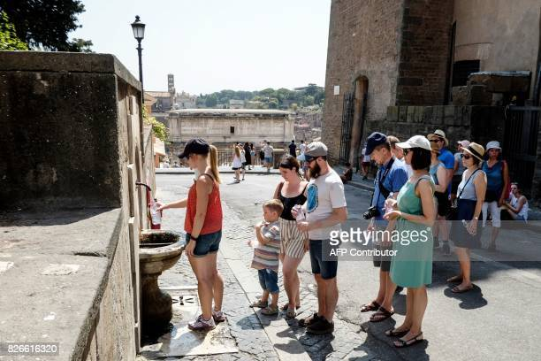 A woman fills a bottle with water from a Nasone a typical Roman fountain in front of the Foro Romano in central Rome on August 5 as temperatures...