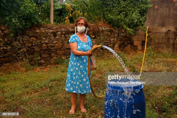 A woman fills a bucket of water to battle a fire approaching her village after a wildfire took dozens of lives on June 19 2017 in a village near...