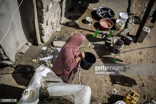 Woman fills a bucket with water brought by a water tank as Palestinians face a water crisis in Gaza City, Gaza on May 9, 2016. Palestinians use most...