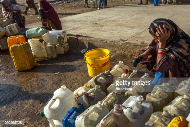A woman fills containers with water in Karachi Pakistan on Saturday Dec 22 2018 Women and children walk miles each day in search forwaterin a...