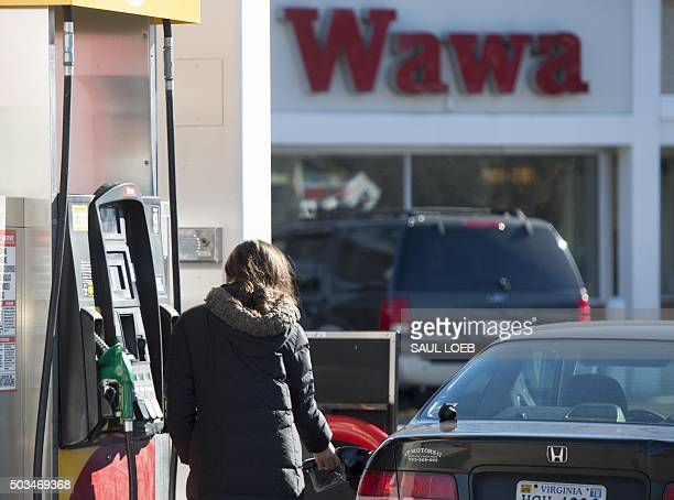 A woman fills her car with gas at a Wawa gas station in Woodbridge Virginia January 5 2016 Oil prices fell further January 5 as the crude supply glut...