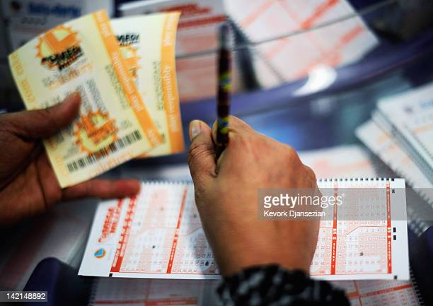 A woman fills out a Mega Millions lottery ticket form at Liquorland on March 30 2012 in Covina California The Mega Millions jackpot has reached a...
