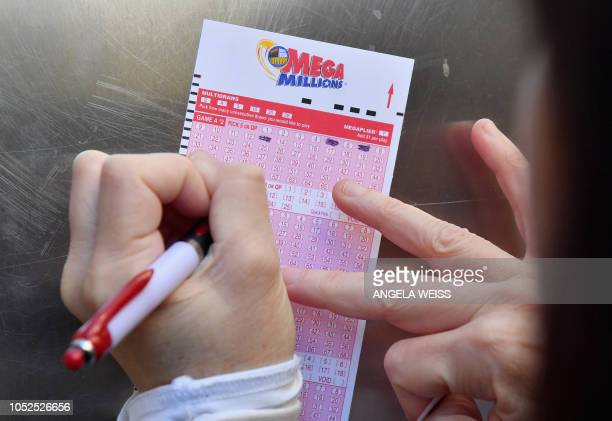 A woman fills out a Mega Millions lottery ticket on October 19 2018 in New York City The Mega Millions jackpot is currently up to $970 million