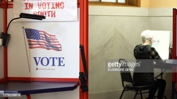 Woman fills out her ballot at the early voting station in the courthouse of Jasper County in Newton, Iowa on October 15, 2020. - Though she's a...