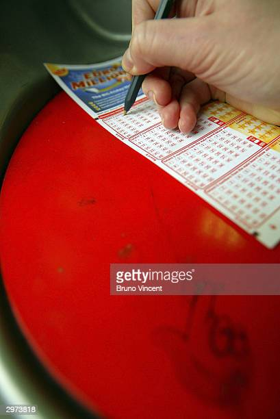A woman fills out her ticket for the Euromillions first draw February 12 2004 in central London England The first draw of the new Euromillions...