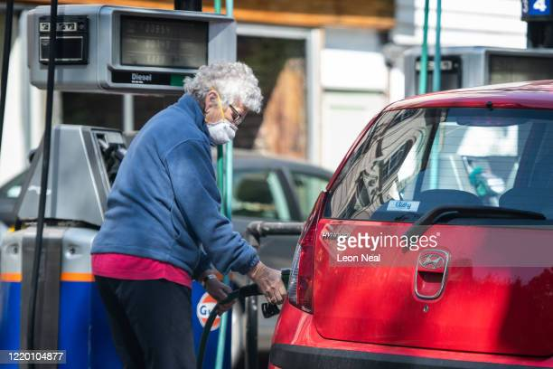 Woman fills the petrol tank of her car at an independent petrol station on April 21, 2020 in London, England. The slump in demand for oil due to the...