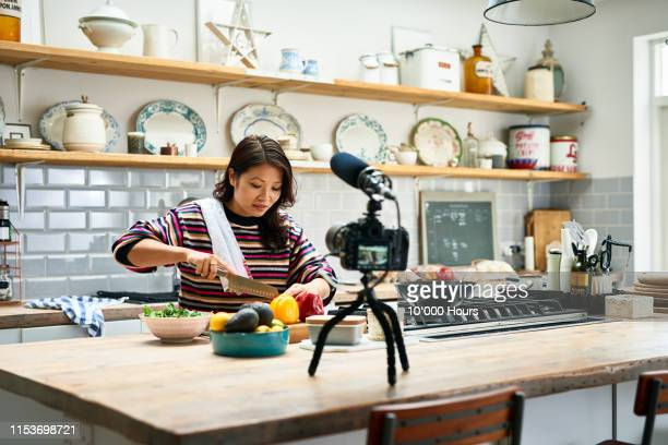 woman filming food vlog at home in kitchen - tutorial stock pictures, royalty-free photos & images