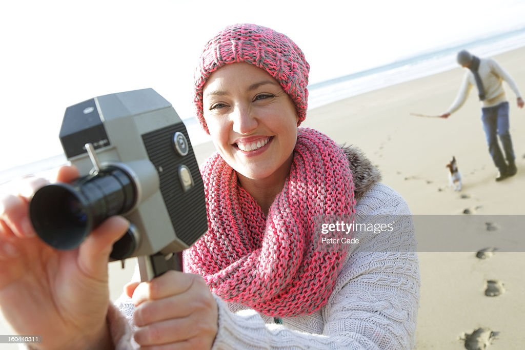 Woman filming on beach with man and dog : Stock Photo