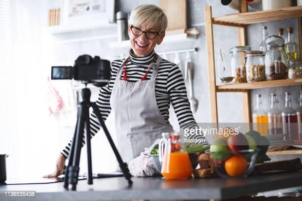 vrouw filmen video voor haar voedsel kanaal - influencer stockfoto's en -beelden