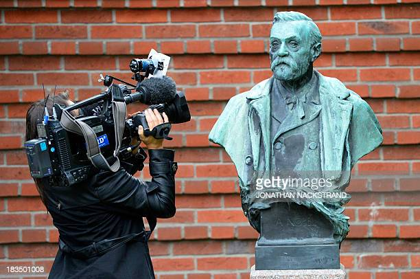 A woman films a statue of Swedish inventor of dynamite Alfred Nobel prior to a press conference to announce the laureate of the 201 Nobel Prize in...