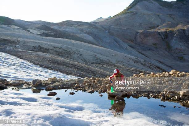 a woman filtering water while on a backpacking trip. - bellingham stock pictures, royalty-free photos & images