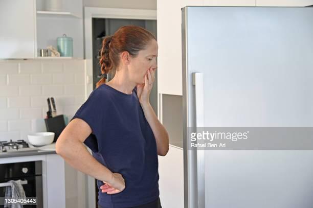 woman finding out that fridge is empty - rafael ben ari stock-fotos und bilder