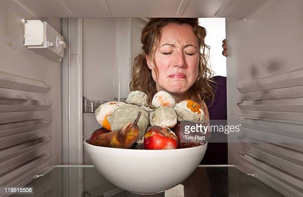 woman finds bowl of rotting fruit in the fridge. - olor desagradable fotografías e imágenes de stock