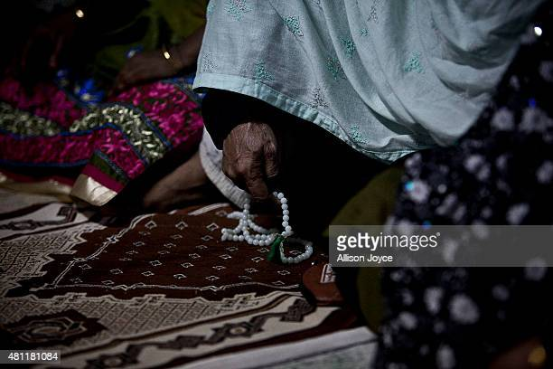 A woman fingers prayer beads at Baitul Mukarram the National Mosque on Eid AlFitr July 18 2015 in Dhaka Bangladesh Muslims around the world are...
