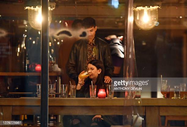 A woman finishes her drink in a bar in Manchester city centre northwest England on October 22 2020 ahead of new coronavirus restrictions coming into...