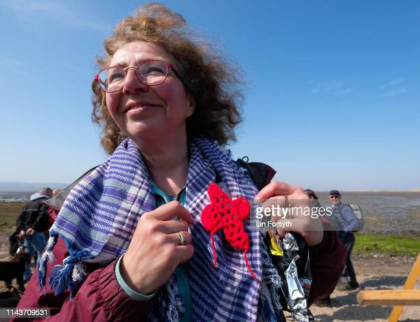 Woman finishes her pilgrimage as she joins other pilgrims celebrating Easter by carrying wooden crosses over the tidal causeway to Lindisfarne during...
