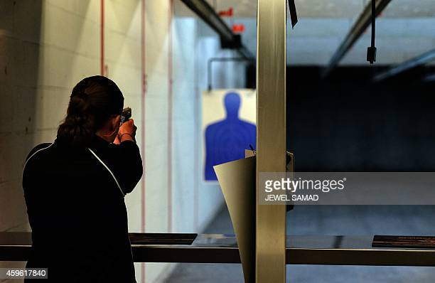 A woman fires a gun at the Ultimate Defense Firing Range and Training Center in St Peters Missouri some 20 miles west of Ferguson on November 26 2014...