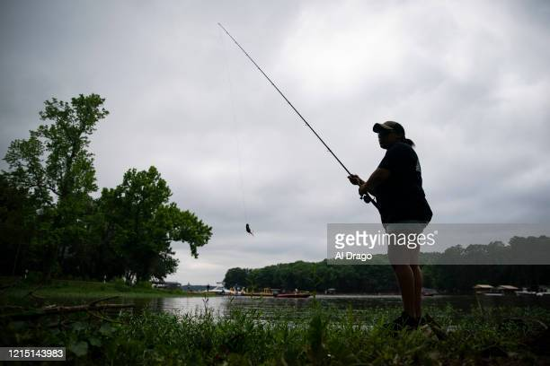 Woman fishes on Lake Tillery near the Lilly's Bridge Marina on Memorial Day, May 25, 2020 in Mount Gilead, North Carolina. Despite overcast skies,...