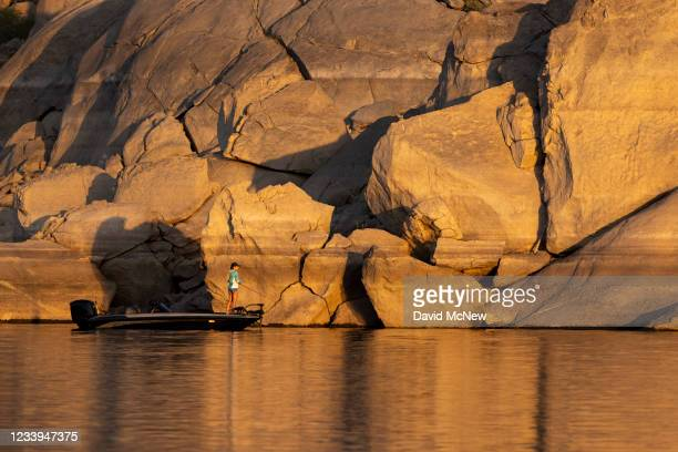 Woman fishes the diminishing waters of Lake Isabella, which is at 13% capacity and falling, on July 12, 2021 near Lake Isabella, California....