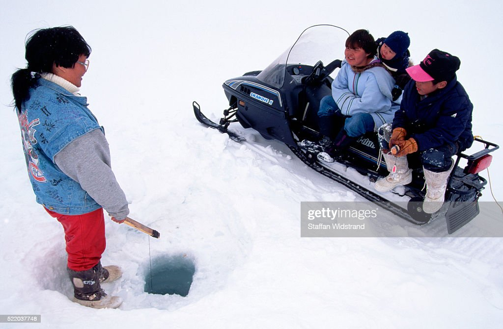 Woman Fishing on Frozen Lake : Stock Photo