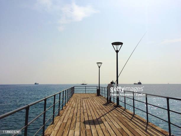 woman fishing on pier over sea against sky - pier stock pictures, royalty-free photos & images