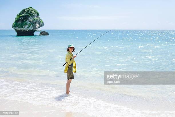Woman fishing on tropical beach, Okinawa, Japan