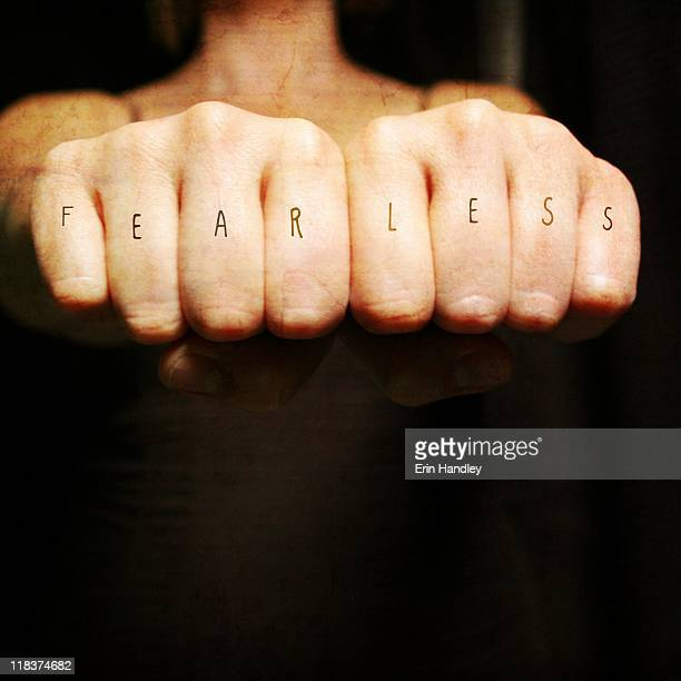 Woman fists with fearless across the knuckles