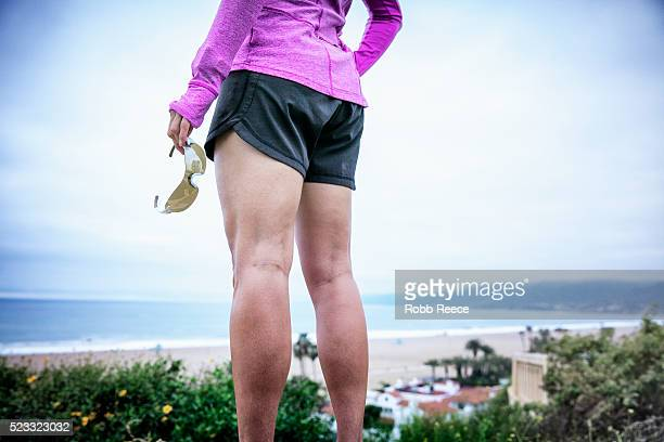 a woman fitness runner holding sunglasses and standing, overlooking the beach in california - robb reece stock pictures, royalty-free photos & images
