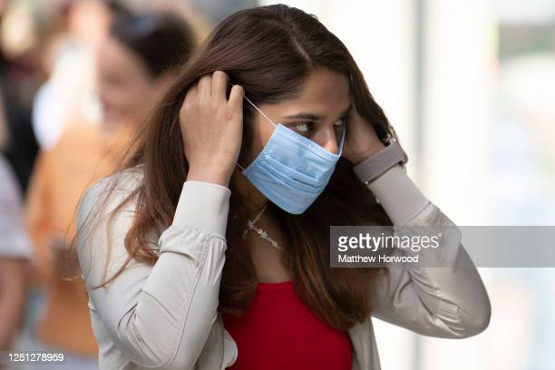 Woman fits a surgical face mask before entering a Zara store as non-essential shops open for the first time since the start of lockdown on June 22,...
