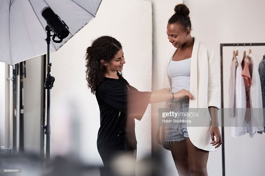 Woman fitting clothes on model in Photo Studio : Stock Photo