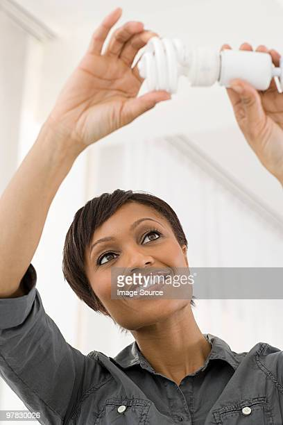 woman fitting lightbulb - energy efficient lightbulb stock photos and pictures